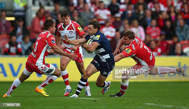 Tom Arscott of Sale Sharks cuts between Henry Trinder and Rupert Harden of Gloucester during the Aviva Premiership match between Gloucester and Sale...