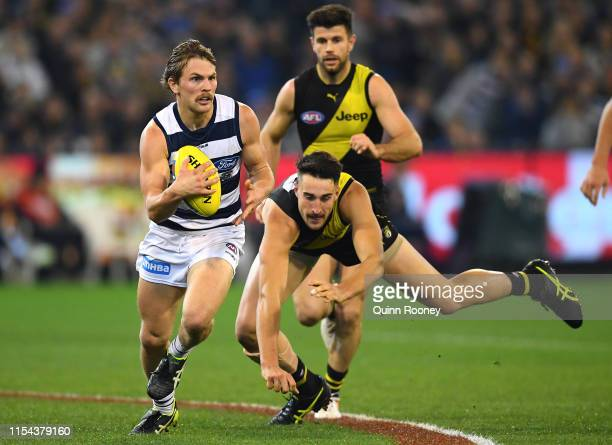 Tom Atkins of the Cats breaks free of a tackle by Ivan Soldo of the Tigers during the round 12 AFL match between the Richmond Tigers and the Geelong...