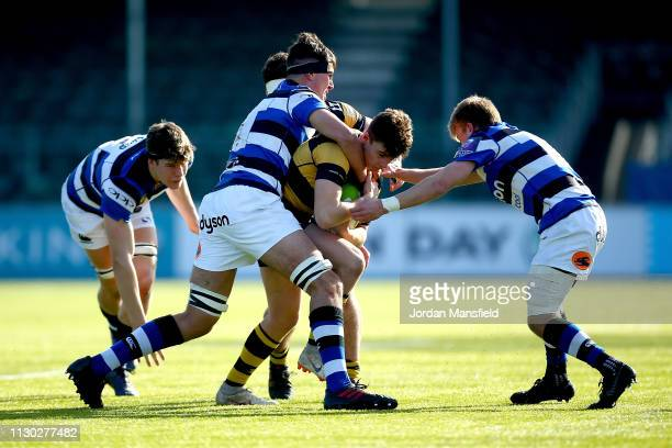 Tom Bacon of Wasps u18's is tackled by Ewan Richards and Will Cook of Bath u18's during the 3/4th Place Playoff match between Bath U18's and Wasps...