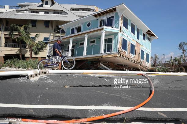 Tom Bailey walks his bike past a home that was carried across a road and slammed up against a condo complex as Hurricane Michael passed through the...
