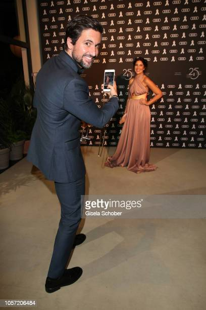 Tom Beck takes a photo of his wife Chryssanthi Beck during the 25th Opera Gala at Deutsche Oper Berlin on November 4 2018 in Berlin Germany