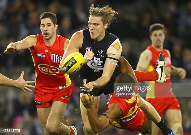 Tom Bell of the Blues is tackled by Touk Miller of the Suns during the round 13 AFL match between the Carlton Blues and the Gold Coast Titans at...