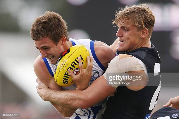 Tom Bell of the Blues tackles Shaun Atley of the Kangaroos during the round one AFL NAB Cup match between the North Melbourne Kangaroos and the...