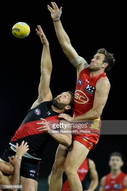 Tom Bellchambers of the Bombers competes for the ball against Sam Day of the Suns during the round 11 AFL match between the Gold Coast Suns and the...