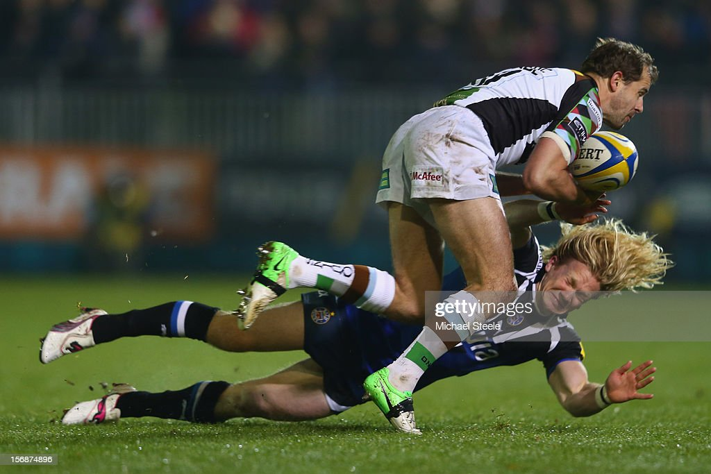 Tom Biggs (R) of Bath falls under the challenge of Nick Evans (L) of Harlequins during the Aviva Premiership match between Bath and Harlequins at the Recreation Ground on November 23, 2012 in Bath, England.