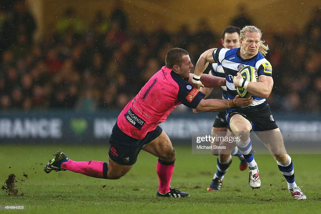 Tom Biggs (R) of Bath sidesteps the challenge of Thomas Davies (L) of Cardiff Blues during the LV Cup match between Bath and Cardiff Blues at the Recreation Ground on January 25, 2014 in Bath, England.