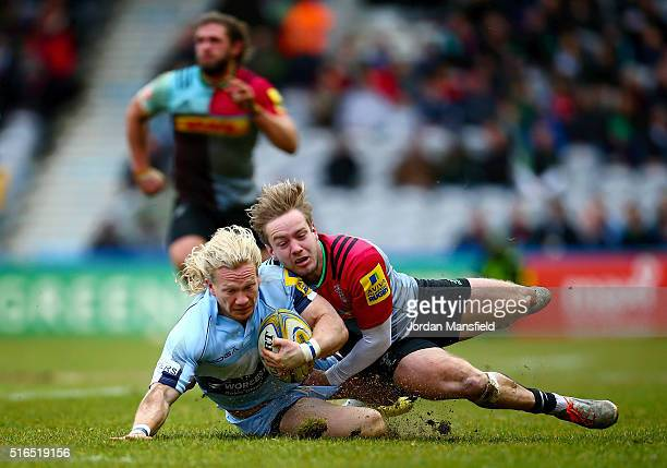 Tom Biggs of Worcester is tackled by Charlie Walker of Harlequins during the Aviva Premiership match between Harlequins and Worcester Warriors at...
