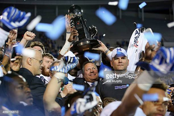 Tom Bowen, Athletic Director of the Memphis Tigers and Head coach Justin Fuente of the Memphis Tigers hold up the AAC championship trophy after a win...