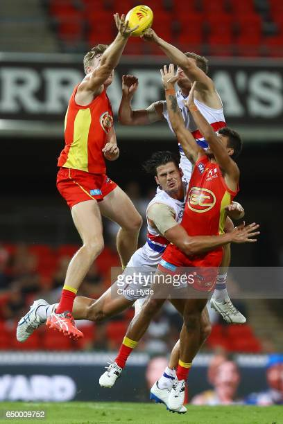 Tom Boyd of the Bulldogs and Callum Ah Chee of the Suns collide during the JLTR Community Series AFL match between the Gold Coast Suns and the...