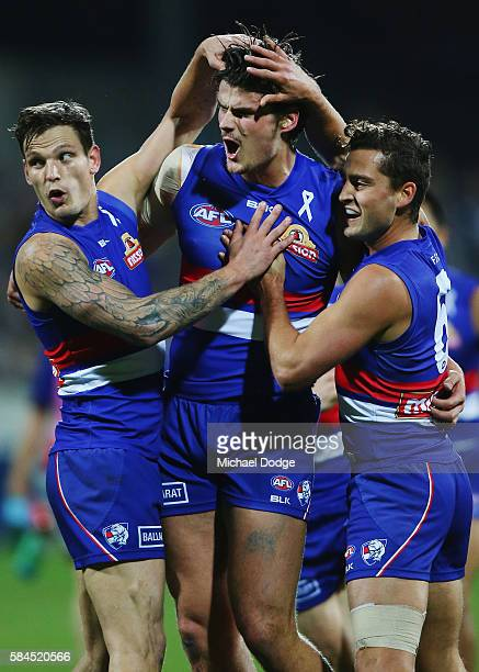 Tom Boyd of the Bulldogs celebrates a goal with Clay Smith and Luke Dahlhaus during the round 19 AFL match between the Geelong Cats and the Western...
