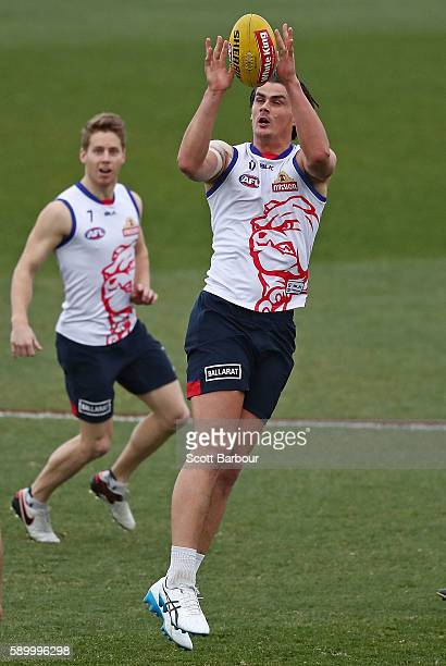 Tom Boyd of the Bulldogs marks the ball as Lachie Hunter of the Bulldogs looks on during a Western Bulldogs AFL training session at Whitten Oval on...