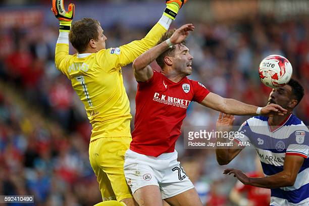 Tom Bradshaw of Barnsley challenges with Alex Smithies of Queens Park Rangers during the Sky Bet Championship match between Barnsley and Queens Park...