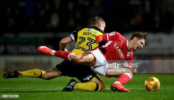 Tom Bradshaw of Barnsley is tackled by Jake Buxton of Burton during the Sky Bet Championship match between Burton Albion and Barnsley at Pirelli...