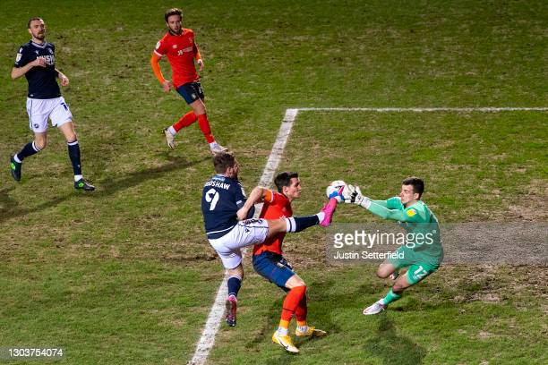 Tom Bradshaw of Millwall battles for possession with Dan Potts and Simon Sluga of Luton Town during the Sky Bet Championship match between Luton Town...