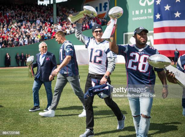 Tom Brady and James White of and the New England Patriots hold Lombardi trophies during a ceremony in recognition of their Super Bowl victory at...