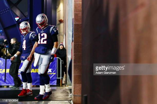 Tom Brady and Jarrett Stidham of the New England Patriots walk to the field before the AFC Wild Card Playoff game against the Tennessee Titans at...