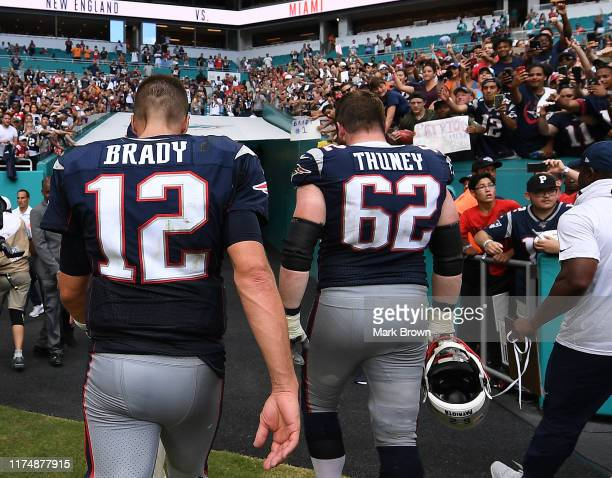 Tom Brady and Joe Thuney of the New England Patriots leave the field after the game against the Miami Dolphins at Hard Rock Stadium on September 15...