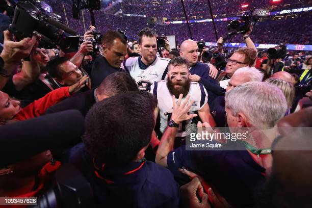 Tom Brady and Julian Edelman of the New England Patriots are swarmed by media after the Patriots defeat the Los Angeles Rams 133 during Super Bowl...