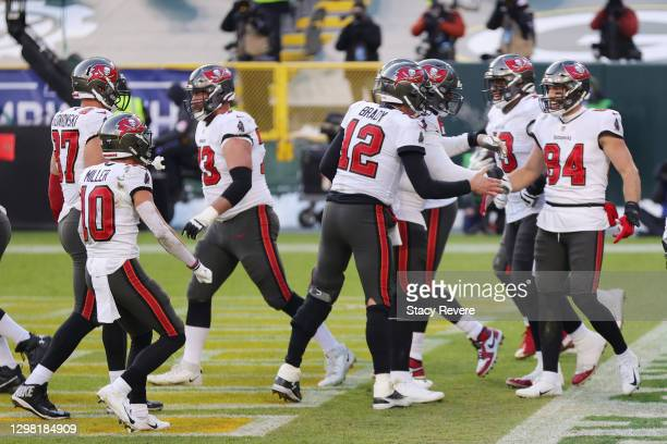 Tom Brady celebrates with Cameron Brate of the Tampa Bay Buccaneers after Brate scored a touchdown in the third quarter against the Green Bay Packers...