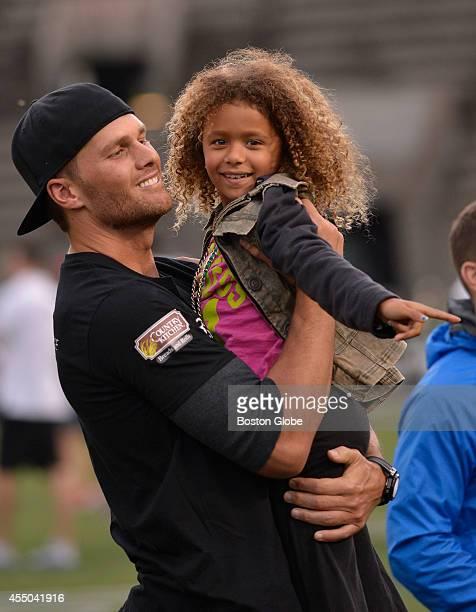 Tom Brady cradles his niece Jordan before Friday May 30th's Best Buddies Challenge at Harvard Stadium in Boston. Participants played alongside Brady,...
