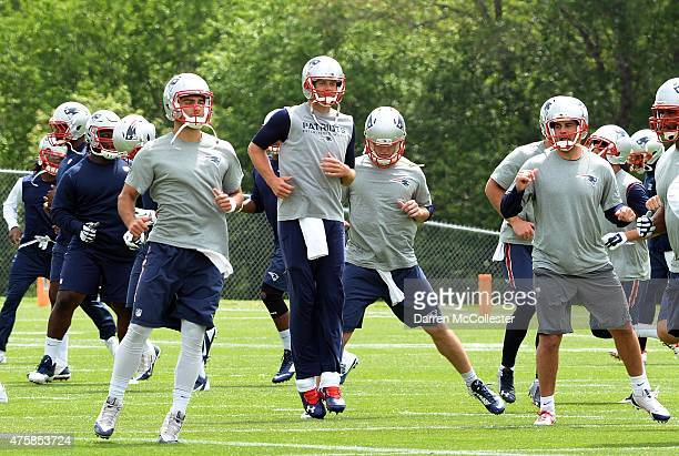 Tom Brady of the New England Patriots and back up quarterback Jimmy Garappolo exercise during organized team activities at Gillette Stadium on June 4...