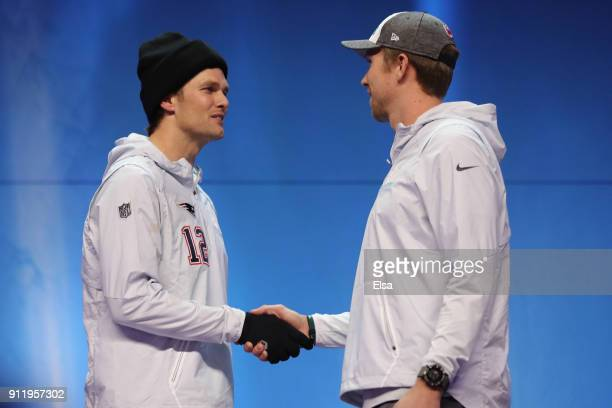 Tom Brady of the New England Patriots and Nick Foles of the Philadelphia Eagles shake hands during Super Bowl Media Day at Xcel Energy Center on...