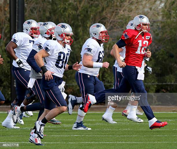 Tom Brady of the New England Patriots and the rest of his teammates warm up before the New England Patriots Super Bowl XLIX Practice on January 28...