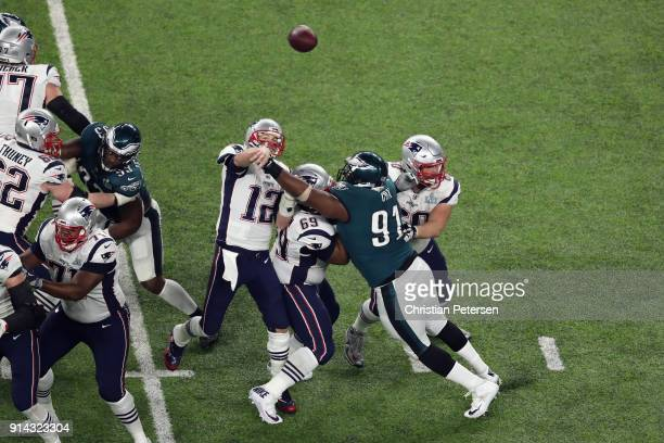 Tom Brady of the New England Patriots attempts a pass defended by Fletcher Cox of the Philadelphia Eagles in the third quarter of Super Bowl LII...