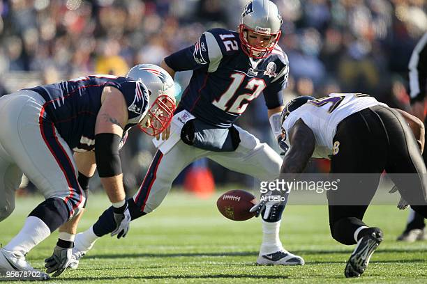 Tom Brady of the New England Patriots attempts to recover his own fumble after the ball was stripped by Terrell Suggs of the Baltimore Ravens during...