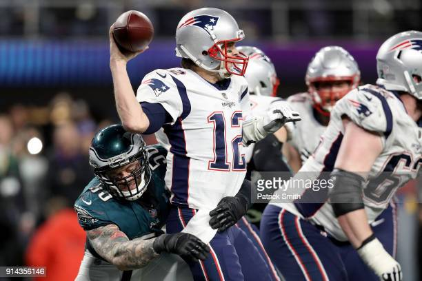 Tom Brady of the New England Patriots attempts to throw a pass under pressure from Derek Barnett of the Philadelphia Eagles during the fourth quarter...
