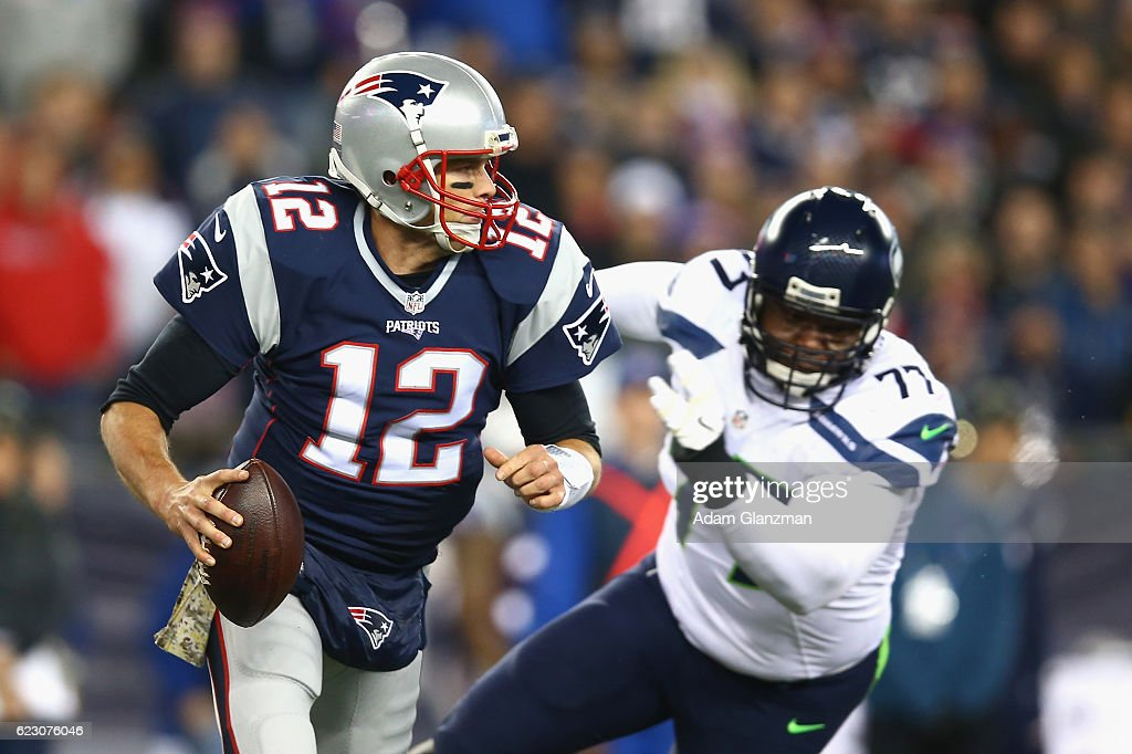 Tom Brady #12 of the New England Patriots carries the ball as he is pressured by Ahtyba Rubin #77 of the Seattle Seahawks during the second quarter of a game at Gillette Stadium on November 13, 2016 in Foxboro, Massachusetts.