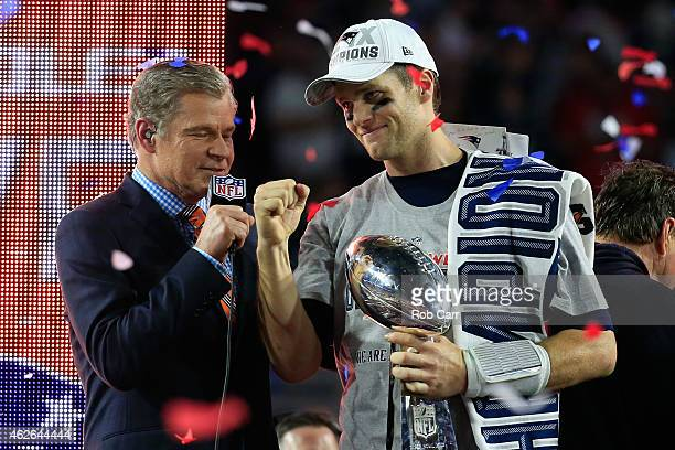 Tom Brady of the New England Patriots celebrates holding the Vince Lombardi Trophy after defeating the Seattle Seahawks as TV personality Dan Patrick...