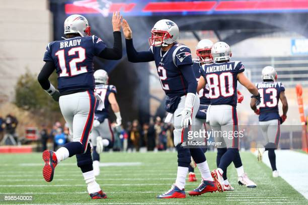 Tom Brady of the New England Patriots celebrates with Brian Hoyer during the first half against the Buffalo Bills at Gillette Stadium on December 24...