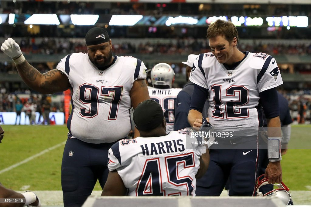 Tom Brady #12 of the New England Patriots celebrates with David Harris #45 on the bench against the Oakland Raiders during the second half at Estadio Azteca on November 19, 2017 in Mexico City, Mexico.
