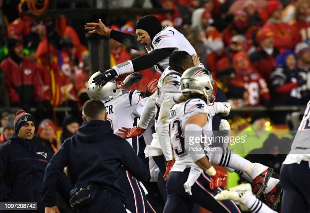 Tom Brady of the New England Patriots celebrates with teammates after defeating the Kansas City Chiefs in overtime during the AFC Championship Game...