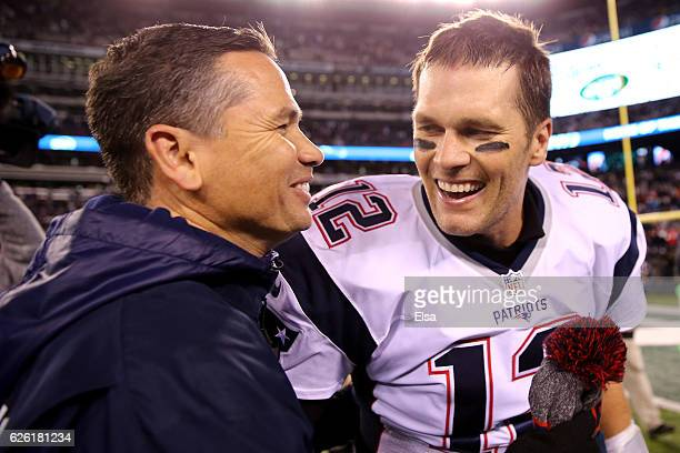Tom Brady of the New England Patriots celebrates with trainer Alex Guerrero after defeating the New York Jets with a score of 22 to 17 at MetLife...