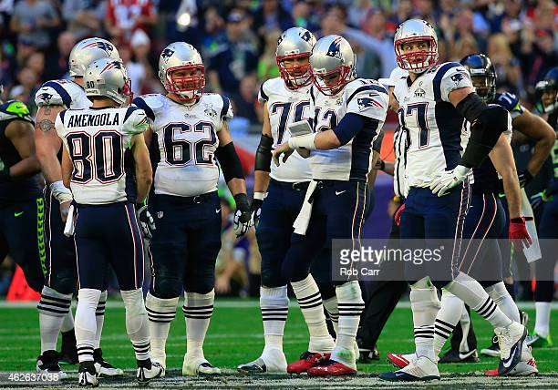 Tom Brady of the New England Patriots checks his play card as Sebastian Vollmer and Rob Gronkowski look on in the first quarter against the New...