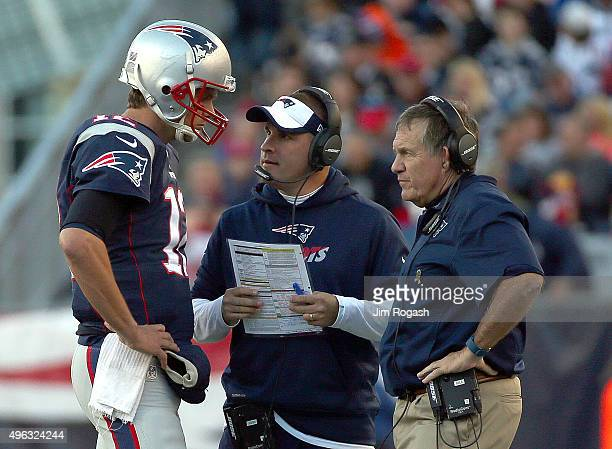 Tom Brady of the New England Patriots confers with Josh McDaniels and Bill Belichick in the second half during a game with the Washington Redskins at...