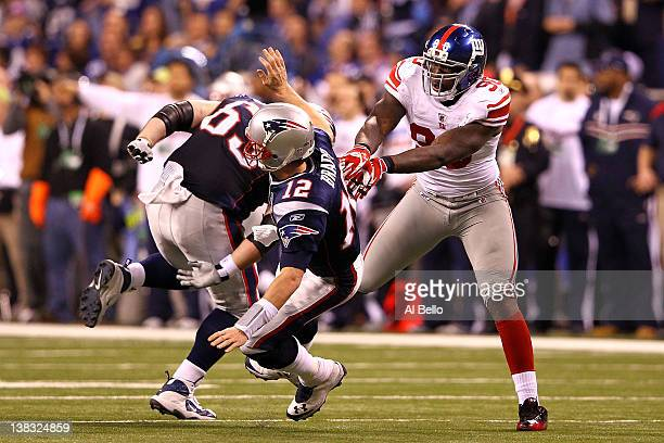 Tom Brady of the New England Patriots falls to the ground after throwing an interception to Chase Blackburn of the New York Giants over Rob...