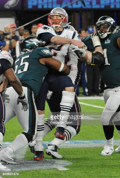 Tom Brady of the New England Patriots fumbles the ball after getting hit by Brandon Graham of the Philadelphia Eagles during Super Bowl LII at US...