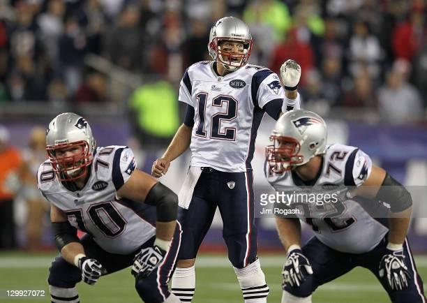 Tom Brady of the New England Patriots gestures as Logan Mankins of the New England Patriots and Matt Light of the New England Patriots hold their...