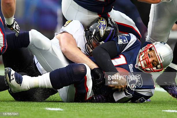 Tom Brady of the New England Patriots gets sacked by Paul Kruger of the Baltimore Ravens in the first quarter during their AFC Championship Game at...