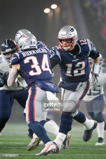 Tom Brady of the New England Patriots hands off to teammate Rex Burkhead as they take on the Tennessee Titans in the first half of the AFC Wild Card...