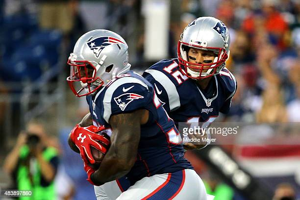 Tom Brady of the New England Patriots hands the ball off to Jonas Gray in the first quarter during a preseason game at Gillette Stadium on August 13...