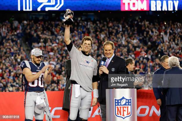 Tom Brady of the New England Patriots holds the Lamar Hunt trophy as he is interviewed by Jim Nantz after the AFC Championship Game against the...