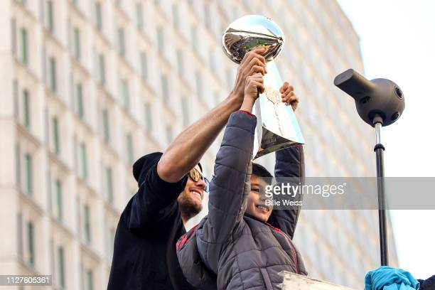Tom Brady of the New England Patriots holds the Vince Lombardi trophy with his son Benjmain Brady during the Super Bowl Victory Parade on February 05...