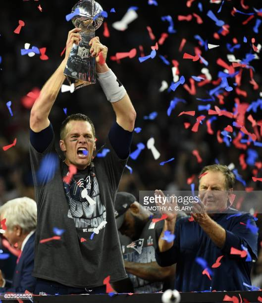 Tom Brady of the New England Patriots holds the Vince Lombardi Trophy as Head coach Bill Belichick looks on after defeating the Atlanta Falcons 3428...
