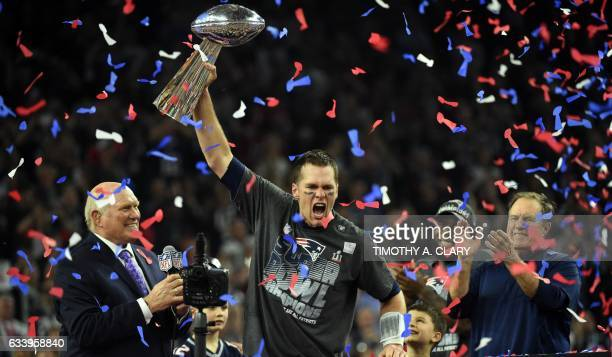 TOPSHOT Tom Brady of the New England Patriots holds the Vince Lombardi Trophy as Head coach Bill Belichick looks on after defeating the Atlanta...