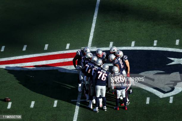 Tom Brady of the New England Patriots huddles with teammates during the game against the Miami Dolphins over the Patriots logo at Gillette Stadium on...