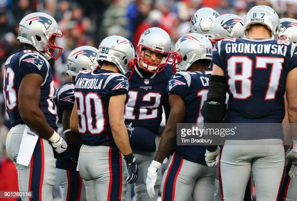 Tom Brady of the New England Patriots huddles with teammates during the game against the Buffalo Bills at Gillette Stadium on December 24 2017 in...